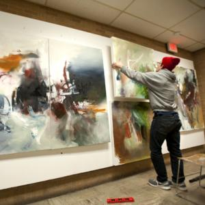 Art student hanging paintings in a campus art gallery